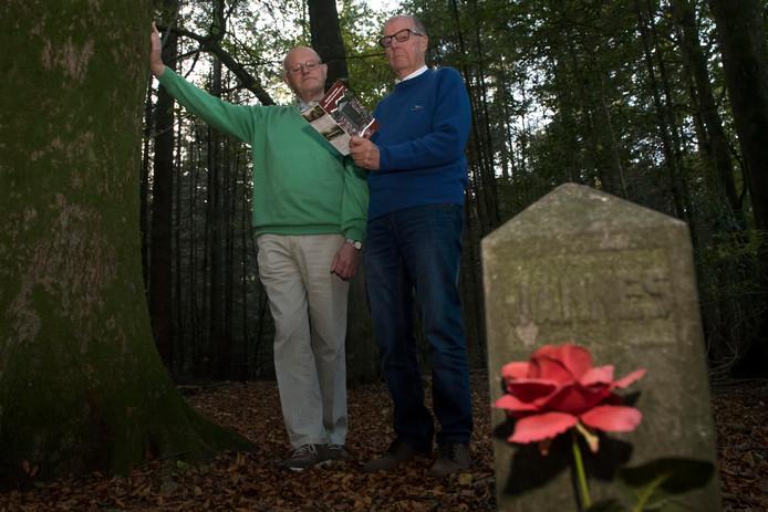 Hans Born (r) en Evert van de Beek (l) bekijken de wandelgids 'Wandelen rond Drie langs ondergrondse geheimen'. Ze staan bij het 'Paaltje van Jannes', het monument van de op 13 december 1944 doodgeschoten broer van Hans.