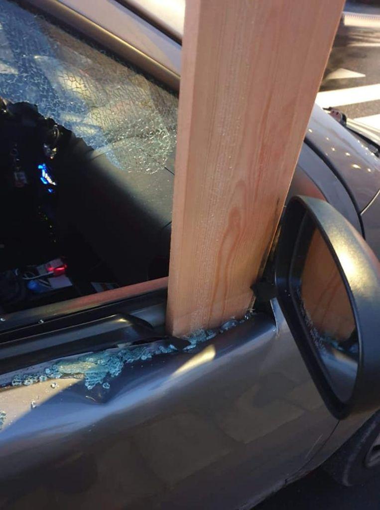Bestuurder ontsnapt aan erger: houten plank doorboort na rukwind portier van auto