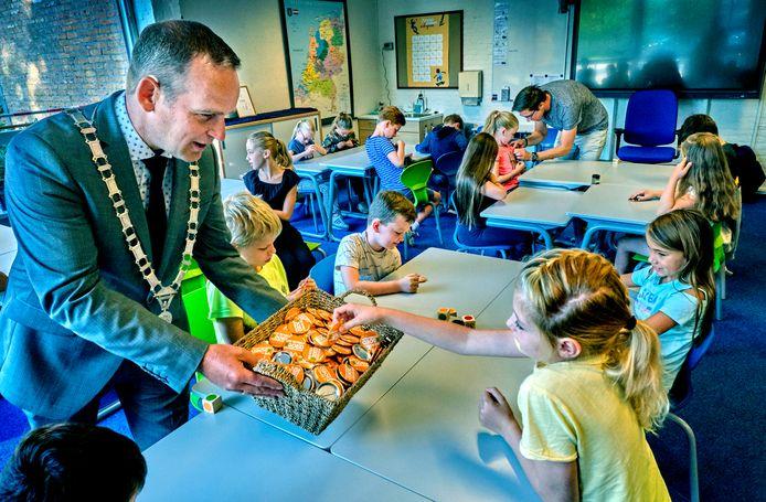 Burgemeester Bram van Hemmen deelt de buttons met de tekst 'Goed voor elkaar' uit op De Schelf tijdens de Week tegen Pesten
