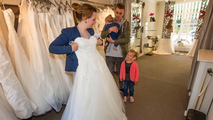 Nicky van den Eijnden (met dochter Nomi op de arm) kijkt toe als zijn vriendin Bianca een trouwjurk bekijkt. Dochter Amy (4) keurt de jurk.