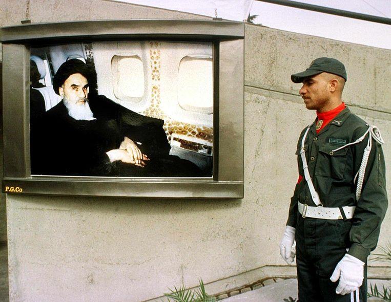Een Iraanse soldaat kijkt op een publieke zender naar beelden van voormalig leider Khomeini, 1999. Beeld anp