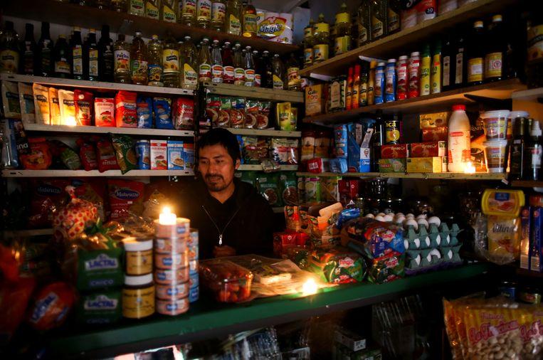Stroom of geen stroom: deze man opent zijn winkel gewoon tijdens de stroomuitval.  Beeld REUTERS