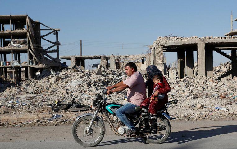 Een gezin rijdt tussen de ruïnes van Kobani, 11 oktober. Beeld null