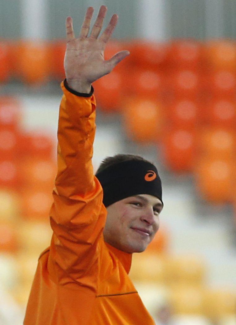 Sven Kramer zwaait, achter hem lege tribunes in de Adler Arena. Beeld ap