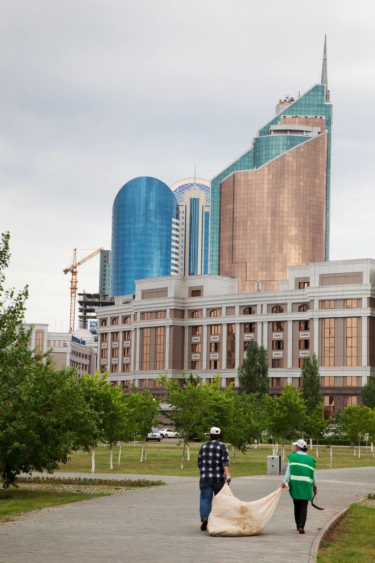 Tuiniers aan het werk met op de achtergrond downtown Astana in aanbouw.   Beeld Ryan Koopmans