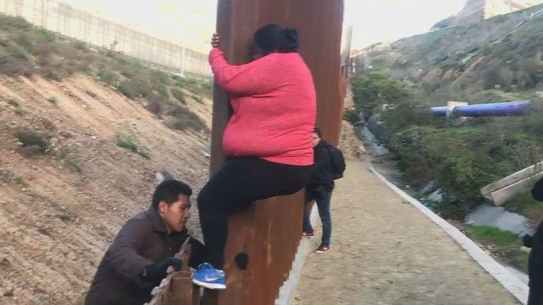 Centraal-Amerikanen klimmen de Amerikaans-Mexicaanse grens over in Tijuana.