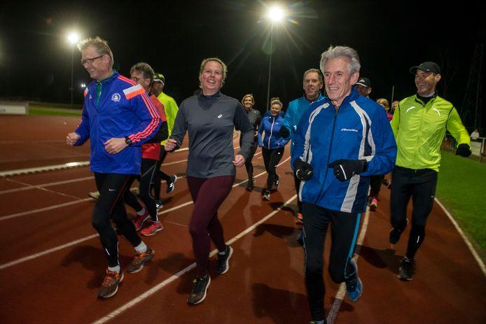 Paul van Uhm (rechtsvoor) met de loopgroep van Athlos op de baan. ,,Je doet wat de trainer zegt he.''