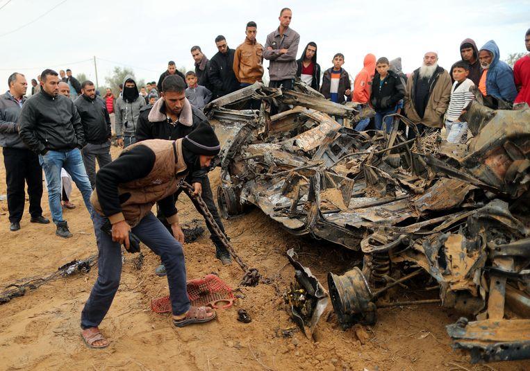 Palestijnen in Khan Younis bekijken wat er over is van de Volkwagen die de elite-eenheid moest achterlaten. Het voertuig is door een Israëlisch gevechtsvliegtuig vernietigd. Beeld REUTERS