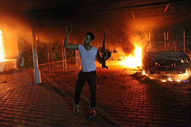 Een gewapende man dinsdagavond bij het Amerikaanse consulaat in Benghazi, Libië. Beeld afp
