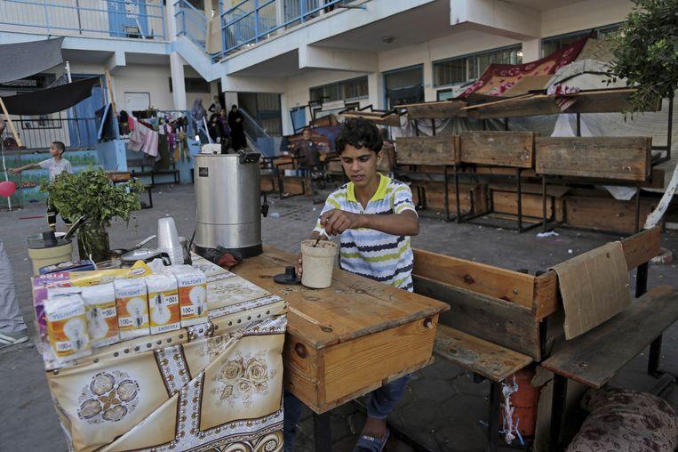 Een Palestijnse jongen verkoopt thee en koffie in de tuin van een VN-school in Gaza. Beeld ap