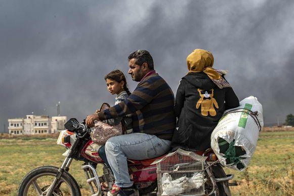 Een Syrische familie ontvlucht de gevechtszone. De rook op de achtergrond is van brandende autobanden die de Koerdische milities gebruiken om het zicht van piloten te bemoeilijken.