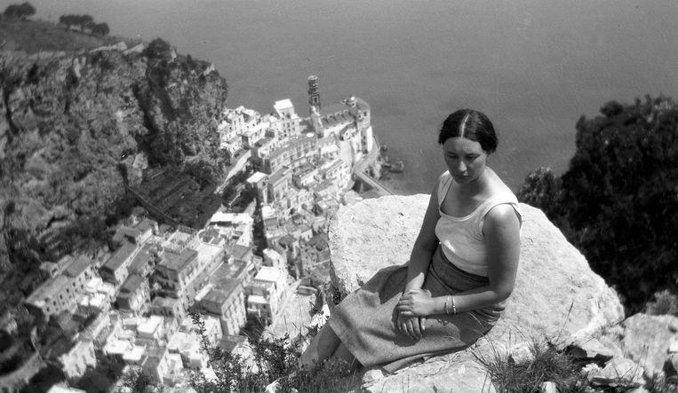 Eschers vrouw Jetta Umiker bij Amalfi in Italië. De foto diende als inspiratie voor 'Metamorphose III' (onder). Beeld RV