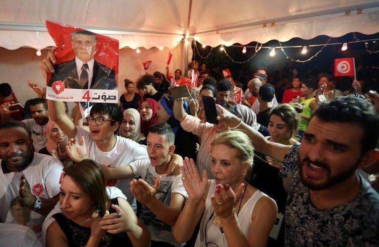 Aanhangers van de gedetineerde kandidaat Nabil Karoui reageren zondagavond opgetogen als de voorlopige uitslag bekend wordt. Karoui werd tweede met 15,5 procent van de stemmen.  Beeld REUTERS