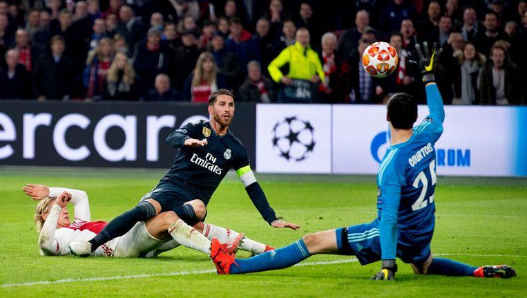 Sergio Ramos en Kasper Dolberg van Ajax met elkaar in duel. Courtois redt op een poging van de spits. Beeld anp