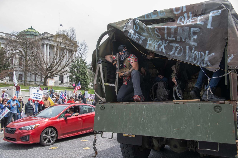 Een man met een zwaar wapen doet mee aan een demonstratie in de staat Pennsylvania tegen de coronamaatregelen die de economie ontwrichten.   Beeld AFP