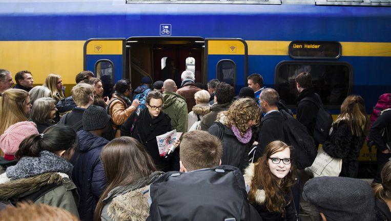 Reizigers proberen ondanks de drukte een plekje te bemachtigen in de trein. Beeld anp