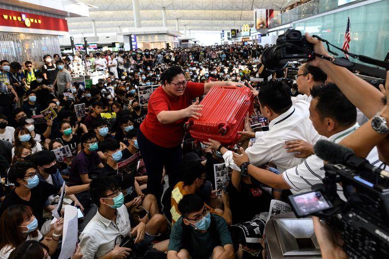 Een reiziger probeert haar koffer aan een beveiligingsmedewerker te geven op het geblokkeerde vliegveld van Hongkong. Beeld AFP