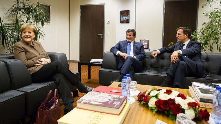 Rutte en Merkel om de tafel met de Turkse premier Davutoglu. Beeld anp