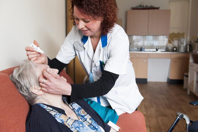 Een verzorgende brengt oogdruppels toe bij een bewoonster van een verzorgingshuis.