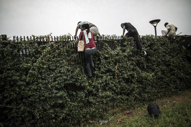 Studenten klauteren over de omheining van de Amerikaanse ambassade in Bujumbura.