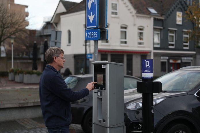Een man voert zijn kenteken in bij een parkeerautomaat in Helmond.