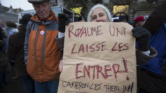 Een betoogster in Calais roept het Verenigd Koninkrijk op de migranten binnen te laten.