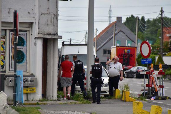 Eén van de aanwezigen (met rood shirt) uit de woning wordt weggeleid door de politie.