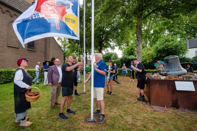 Michel Kooij (links naast de vlaggenmast) helpt de Puttense bevrijdingsvlag hijsen aan het einde van de evacuatiewandeltocht bij monument De Klok in Huissen. Foto: Gerard Burgers