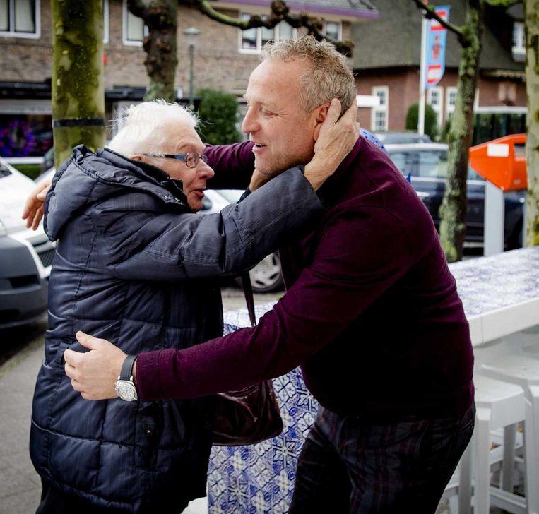 Gordon wordt omhelst tijdens een kerstmiddag die hij voor eenzame ouderen organiseerde. Beeld anp