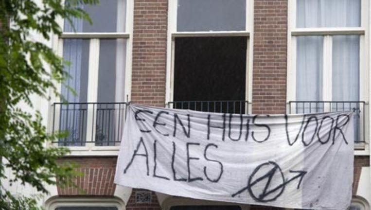 Een spandoek met de tekst 'Een huis voor alles' hangt maandag aan de gevel van een gekraakt pand aan de Commelinstraat in Amsterdam. Tot 1 oktober is kraken niet strafbaar. Op 1 oktober gaat de antikraakwet in. Foto ANP Beeld