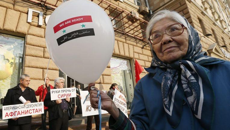 Een vrouw houdt een ballon met daarop een Syrische vlag vast. Beeld epa