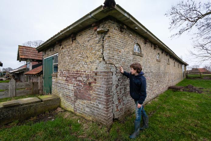 De 13-jarige Pieter Dekker inspecteert de scheuren in de verzakte boerderij in Spanga.