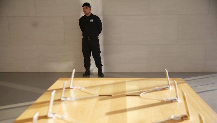 Een winkelbeveiliger houdt de iPhones in de Apple Store in Peking in de gaten. Beeld reuters