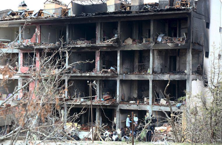 Forensisch experts onderzoeken de puinhopen van het politiecomplex. Beeld reuters