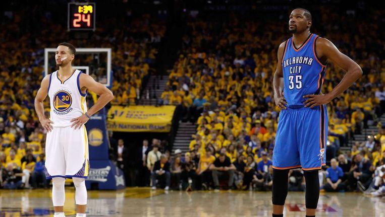Stephen Curry (L) van de Golden State Warriors en Kevin Durant van de Oklahoma City Thunder voor aanvang van de eerste wedstrijd tussen de twee teams in de Western Conference Finals van de NBA play-offs. Beeld afp