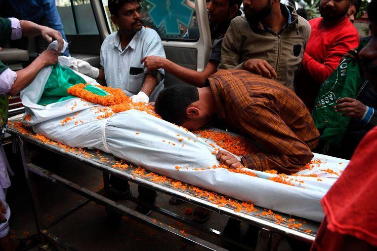 Een man rouwt bij het lichaam van een omgekomen demonstrant.  Beeld AFP