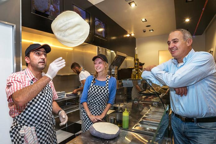George Badrah laat even zien hoe je platbrood maakt. Marije van der Poel en Elias Marun kijken toe.