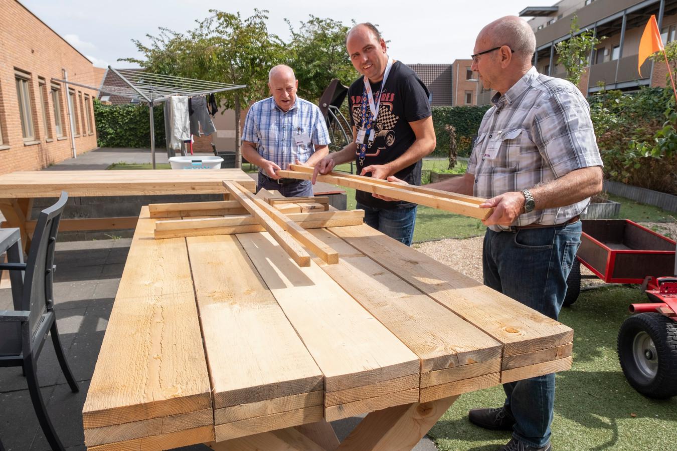 Vrijwilligers Frans van Helvoort (links) en Andre Geleijnse (rechts) zetten een tuintafel in elkaar voor het woonzorgcomplex WMZO in de Trompstraat in Middelburg waar verstandelijk beperkte jongeren wonen. Eén van die jongeren is Danny Dingemanse (midden).