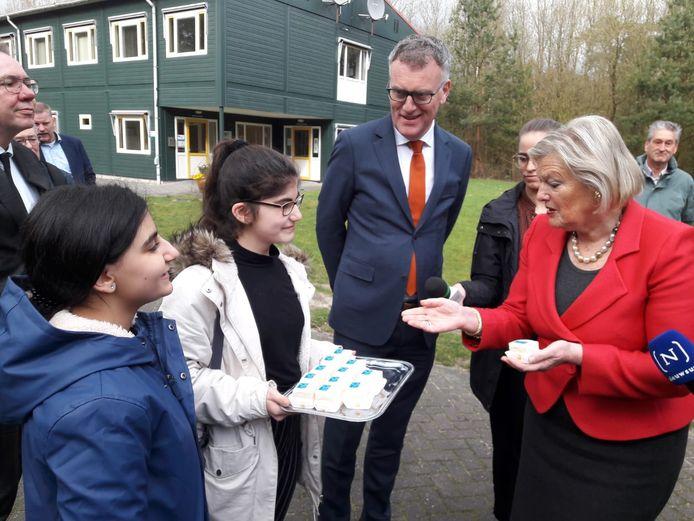 Meisjes van de 25-jarige asielzoekersschool boden staatssecretaris Ankie Broekers-Knol vorige week bij haar bezoek aan het Oisterwijkse azc een gebakje aan. Burgemeester Janssen keek toe.