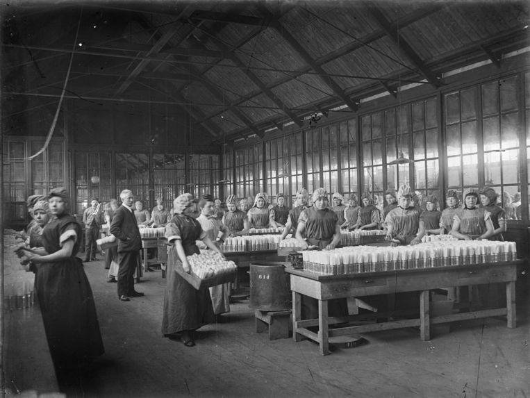 Vullokaal in Weesp waar vrouwen in 1910 handmatig bussen vullen met cacaopoeder. Beeld Nationaal Archief