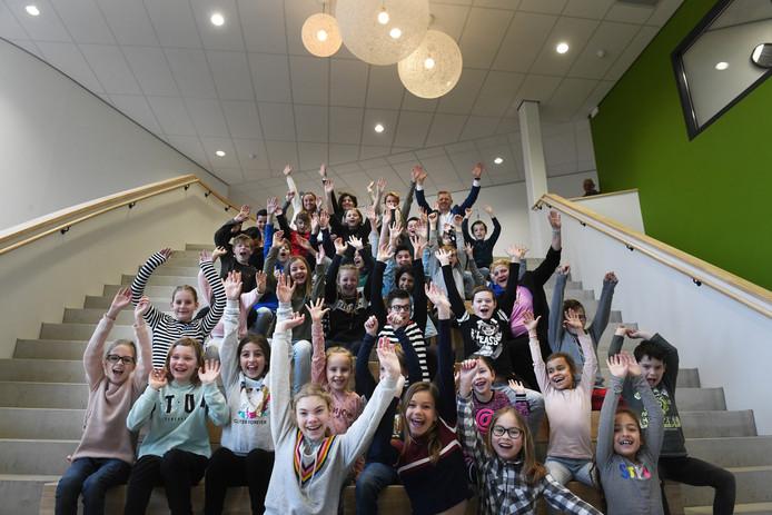 Een klas met leerlingen van De Wegwijzer en een van De Voorhof op de grote podiumtrap van de nieuwe Parkschool in Vianen.