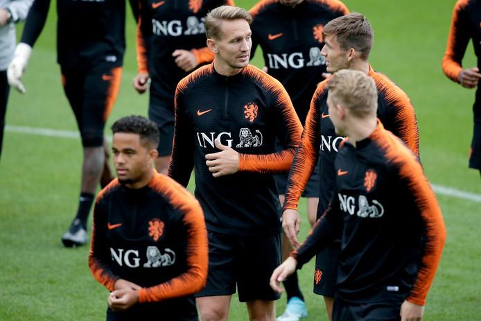 Luuk de Jong (midden) praat met Marten de Roon voor de training van Oranje. \