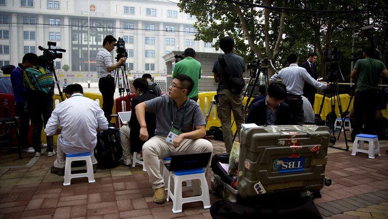 Journalisten wachten zondag bij de rechtbank in de Chinese stad Jinan op de aankomst van Bo Xilai. Beeld null