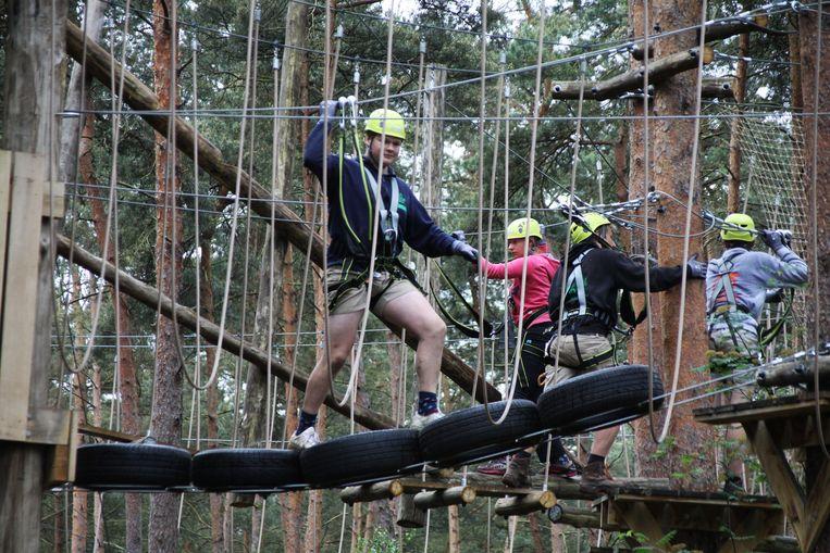 De klimmers zijn beveiligd met touwen en dragen helmen.