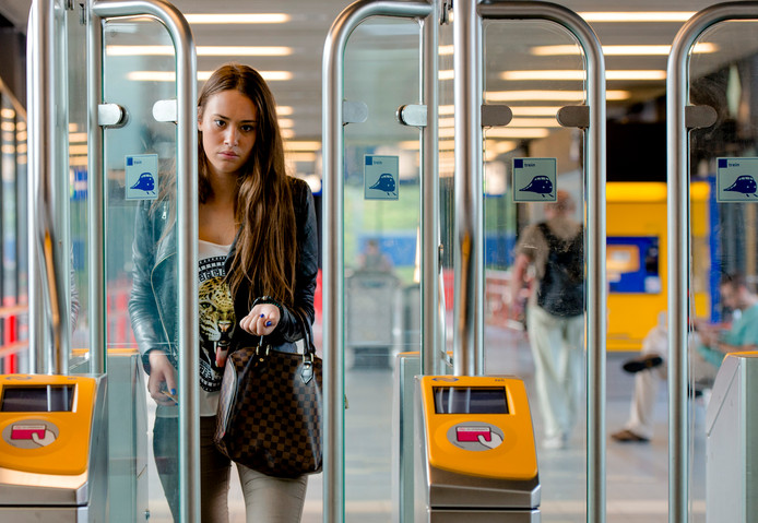 Een reiziger loopt na inchecken door het poortje op station Woerden
