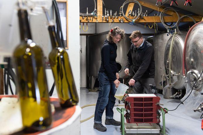 Rudy en Quirien Schellekens filteren de wijn de laatste keer voordat deze wordt gebotteld.