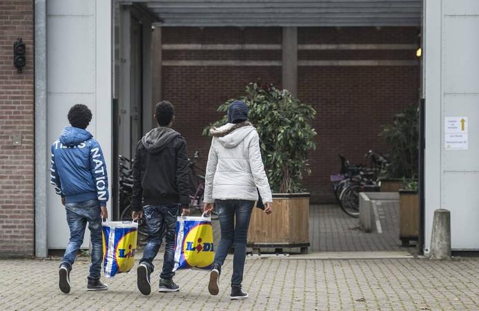 Drie asielzoekers wandelen de hoofdingang van het asielzoekerscentrum aan de Nassausingel binnen. Archieffoto Ron Magielse/het fotoburo