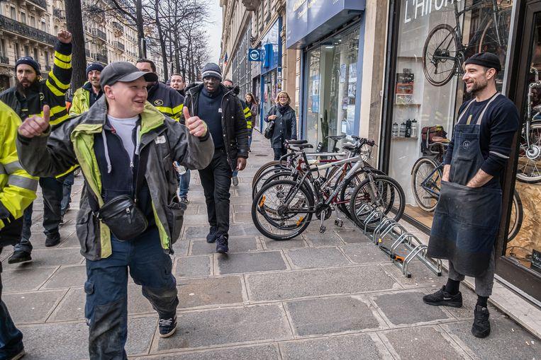 Fietsenmaker/verkoper Kevin Olanier kijkt toe hoe Gele Hesjes langs zijn fietsenwinkel gaan.  Beeld Joris Van Gennip
