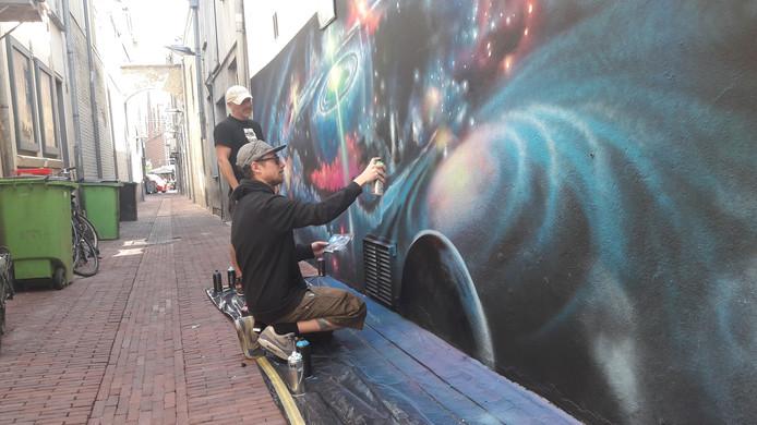 Kunstenaar Tom Linnenbank neemt de muur van de Rozemarijnsteeg onder handen in de Arnhemse binnenstad. Pedro Dentinho van Arnhem Art kijkt toe.
