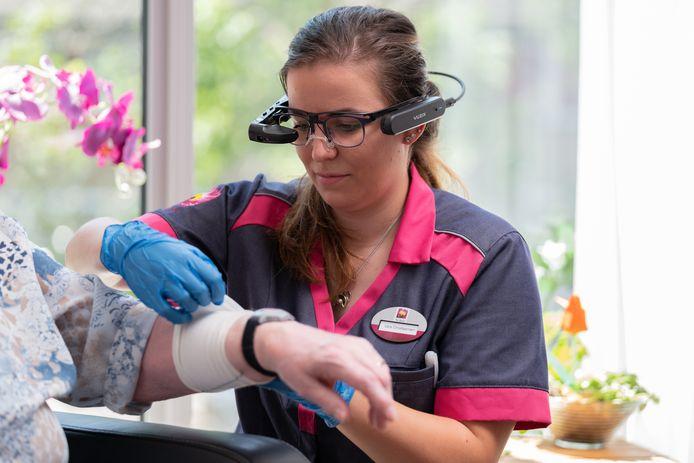 Vera Christiaansen, verpleegkundige in het verpleegkundig interventieteam van Zorggroep Ter Weel in Goes, demonstreert de smart glasses bij een cliënte.